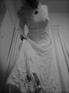 A black and white - image of a woman in a white gown, frayed at the end, spookily stepping towards you skirt in hand - black heart at throat - image 1 of Saintful Sunday - a spooky triptych by Tabitha Rayne