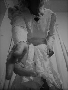 A black and white - image of a woman in a white gown, frayed at the end, spookily kneeling on one knee before you - reaching out a hand to beckon you forth - black heart at throat - image 3 of Saintful Sunday - a spooky triptych by Tabitha Rayne